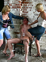 Girlfriends torture a tied up guy in a suburban abandoned building