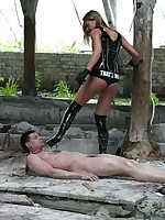 Kinky latex mistress takes her human doggy out for a walk on a leash in the debris of an old building