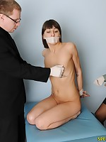 Obedient girl with a taped mouth passing thru an exam